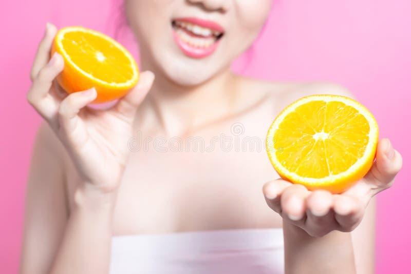 有橙色概念的亚裔妇女 微笑和拿着桔子的她 秀丽面孔和自然构成 隔绝在桃红色背景 免版税图库摄影