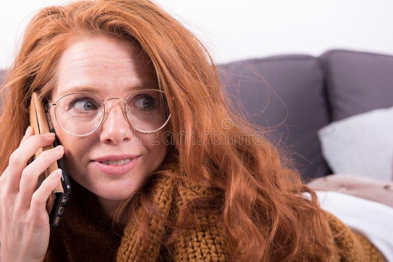 有橙色毛线衣的美丽,红发妇女谈话在b 库存图片