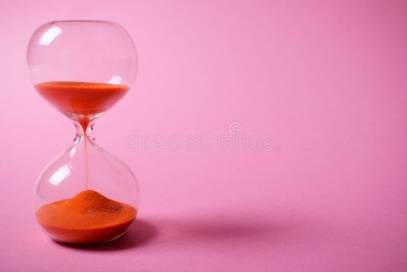 有橙色沙子的滴漏在桃红色背景 免版税库存照片