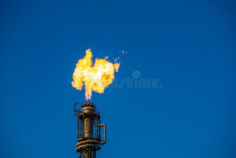 有橙色火和蓝天的烟囱 库存图片