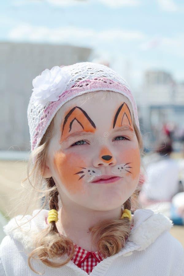 有橙色狐狸面孔绘画的小美丽的女孩  免版税库存图片