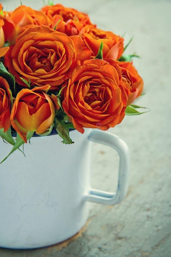 有橙色玫瑰花束的白色杯子  库存图片