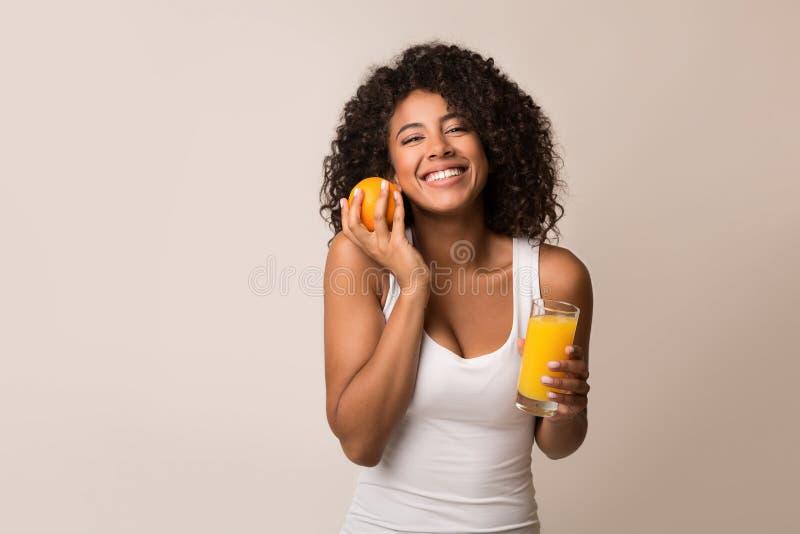 有橙色的非裔美国人的女孩和杯汁液 免版税库存照片