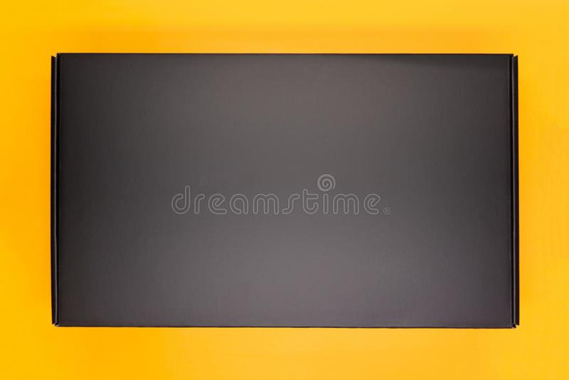 有橙色盒盖的典雅的箱子礼物的栓与与一把美好的弓的一条黑和橙色丝带 库存照片