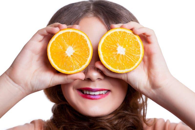 有橙色看照相机的切片的年轻美丽的滑稽的女孩和构成和发型 免版税库存图片