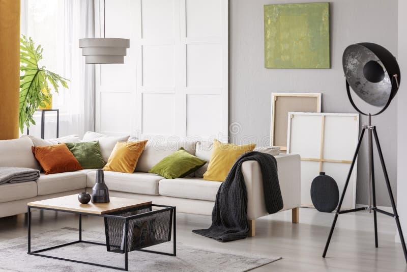 有橙色绿色和黄色枕头的白色典雅的壁角沙发在时髦的客厅内部与现代咖啡桌和indust 免版税库存图片