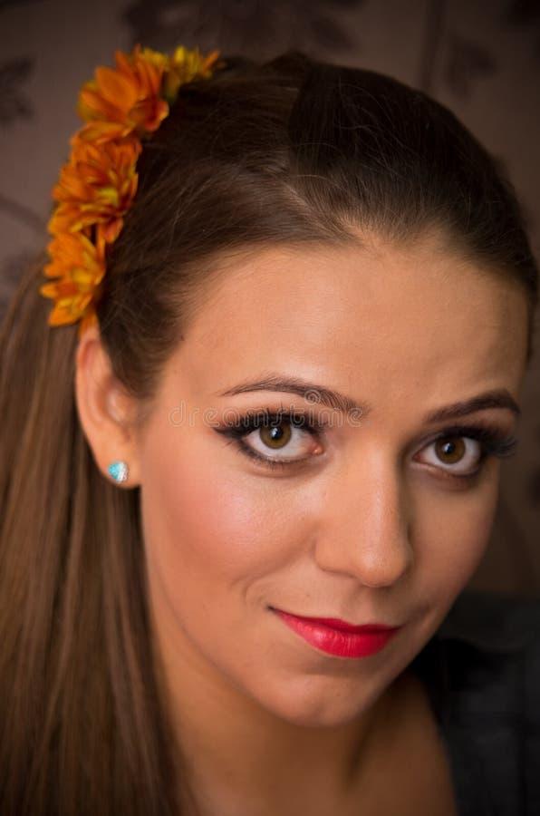 有橙色花的妇女在头发 免版税库存图片