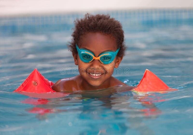 有橙色袖子浮游物的小非洲孩子 免版税图库摄影