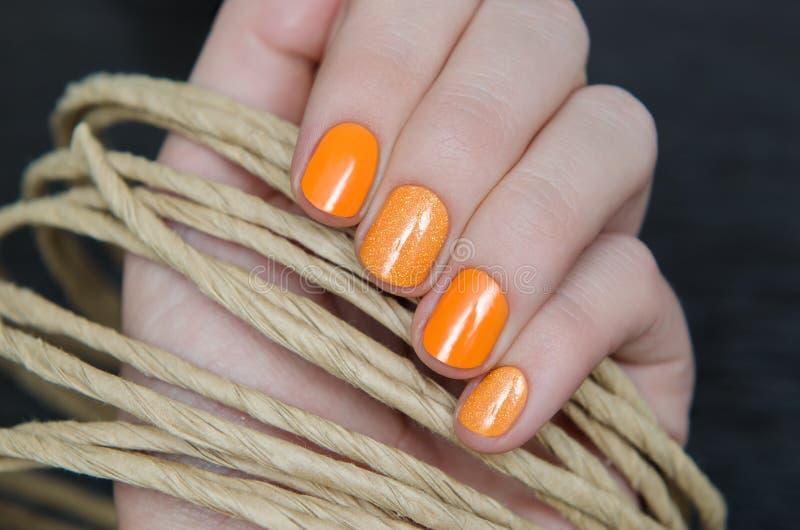 有橙色钉子设计的美好的女性手 免版税库存图片