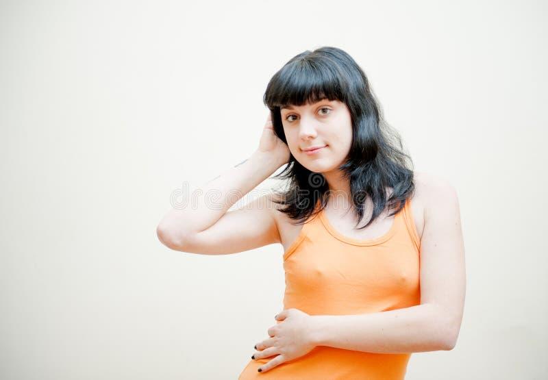 有橙色T恤杉画象的少妇 免版税库存照片