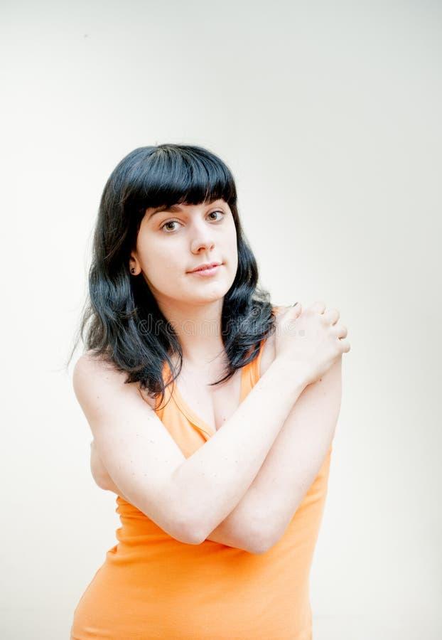 有橙色T恤杉画象的少妇 免版税库存图片
