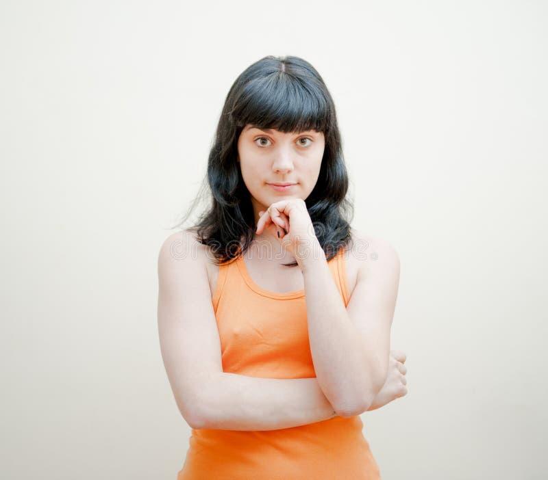 有橙色T恤杉画象的少妇 库存图片