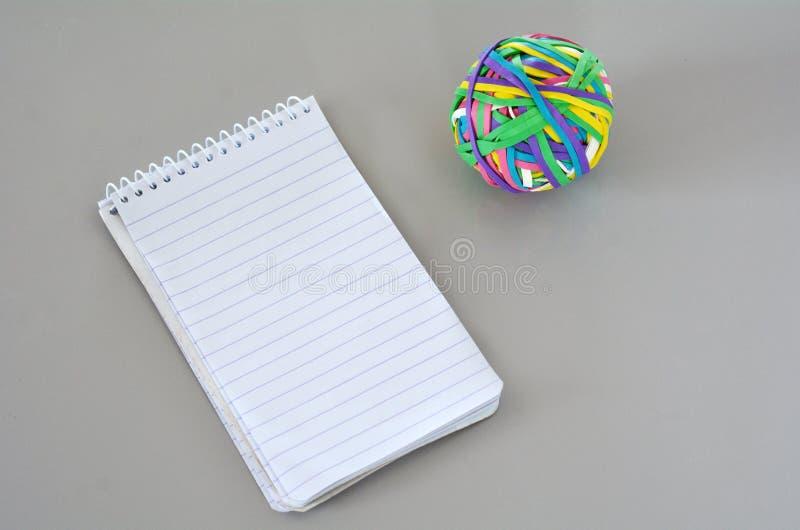 有橡皮筋儿球的笔记本 免版税库存图片