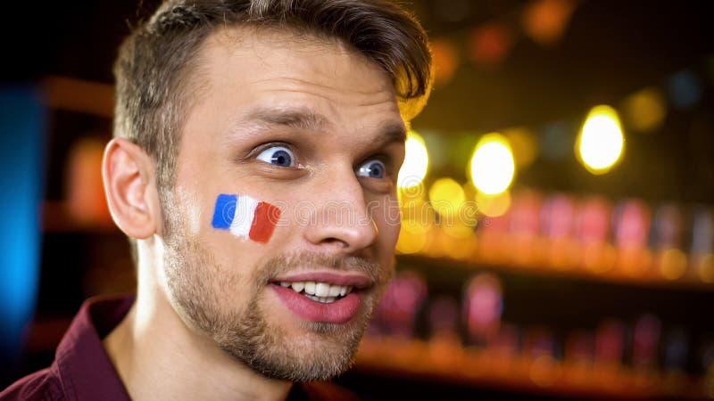 有欢欣支持法国参加者的看着电视展示的帅哥 图库摄影