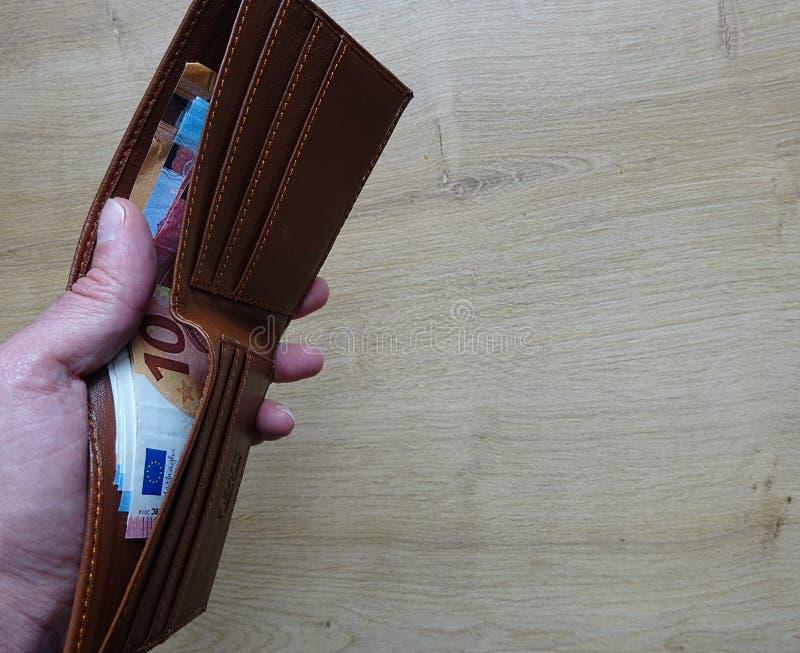 有欧元欧洲纸币钞票的布朗皮革钱包在手中 免版税库存照片