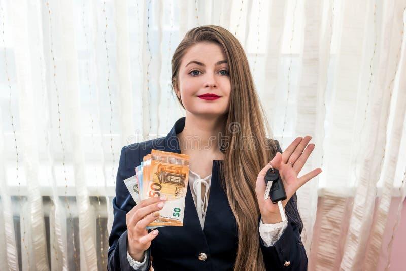 有欧元钞票和汽车钥匙的美丽的经销商 免版税库存照片