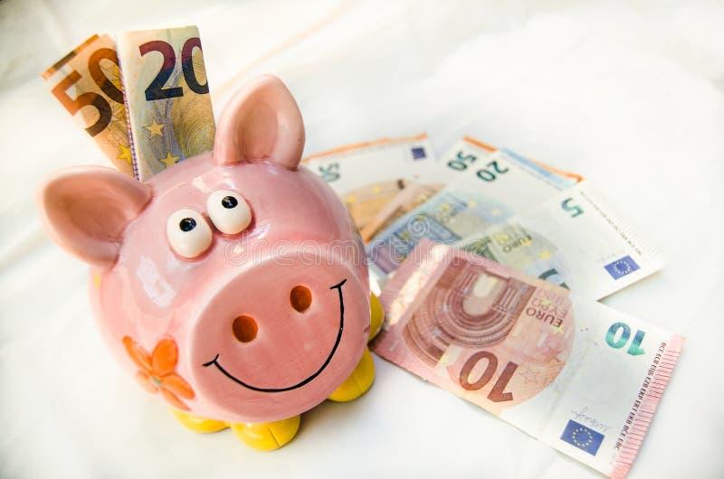 有欧洲储款的桃红色存钱罐在白色backround 免版税库存图片