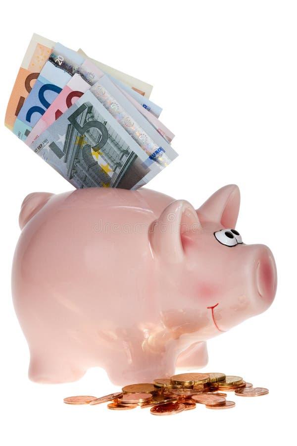 有欧洲钞票的桃红色存钱罐 免版税库存照片
