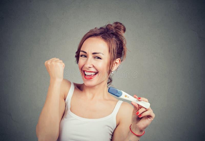 有正面妊娠试验的激动的妇女 免版税库存图片