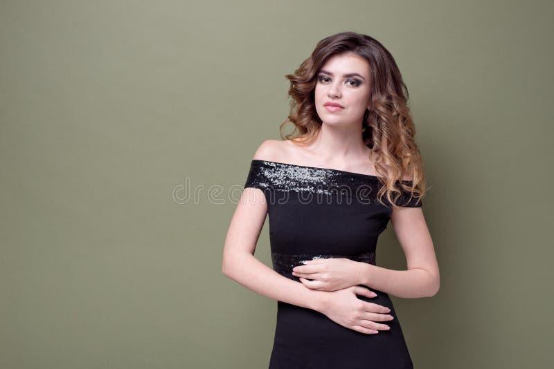 有正面微笑的,微笑愉快的高兴女性广泛地,穿戴在有衣服饰物之小金属片的黑礼服,在绿色墙壁 库存图片