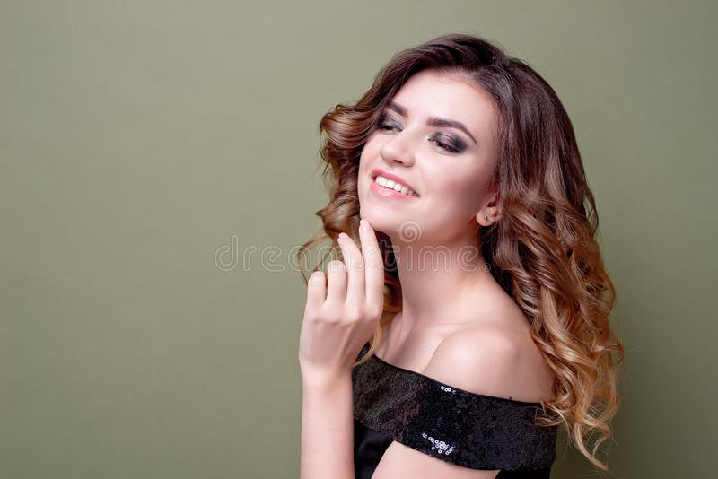 有正面微笑的,微笑愉快的高兴女性广泛地,穿戴在有衣服饰物之小金属片的黑礼服,在绿色墙壁 免版税库存图片