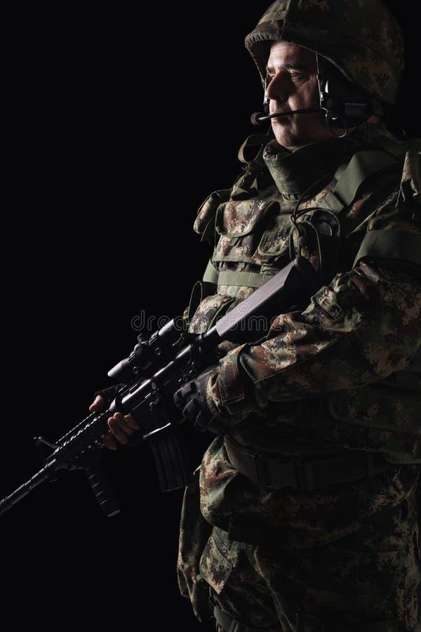 有步枪的特种部队战士在黑暗的背景 免版税库存照片