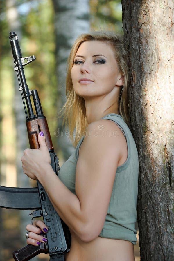 有步枪的年轻金发碧眼的女人 库存照片