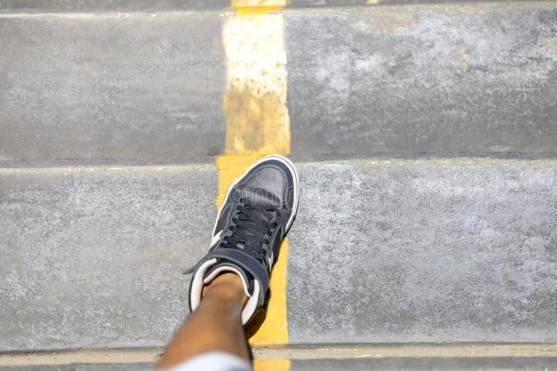 有步行沿着向下有黄线的公开台阶的长的运动鞋的人腿在城市 库存照片