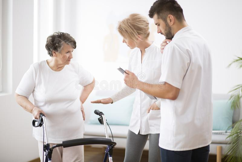 有步行者的灰色资深夫人在与专业女性医生和男性护士的物理疗法期间 免版税库存照片