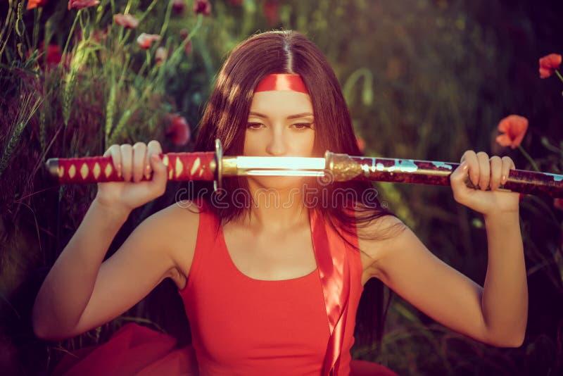 有武士剑的亚裔妇女在自然 免版税库存照片