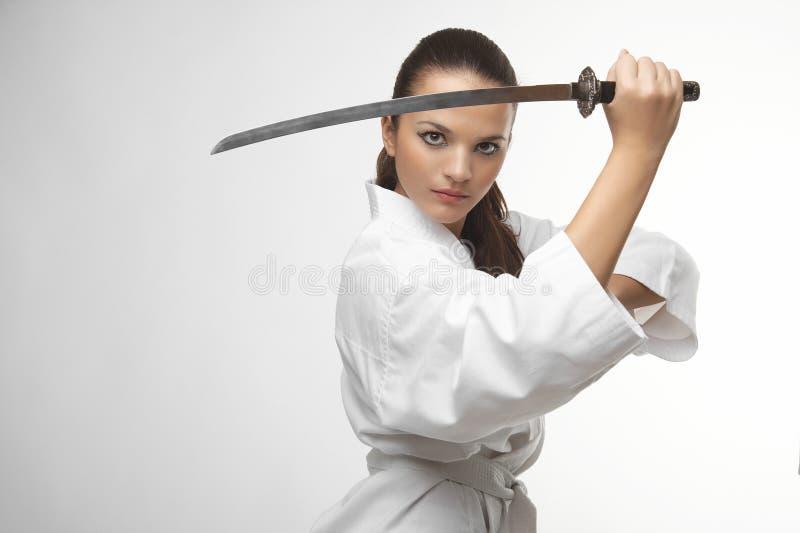 有武士剑的可爱的年轻性感的妇女 免版税库存照片