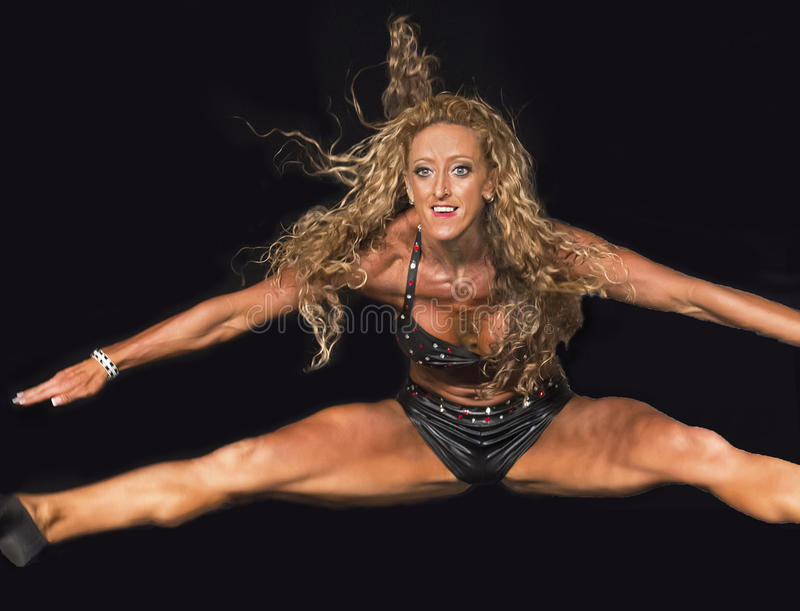 有歪歪卷曲的金发的高飞的健身运动员 图库摄影