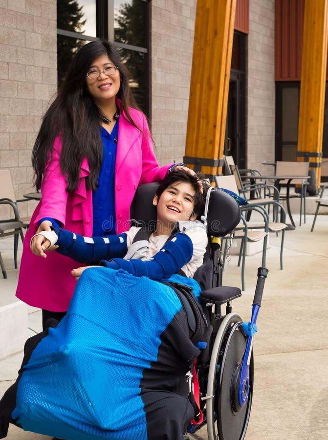 有残疾11岁的儿子的母亲户外轮椅的 免版税库存图片
