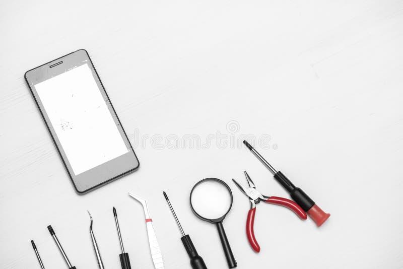 有残破和破裂的屏幕的智能手机有为修理的工具的在白色背景 免版税库存图片