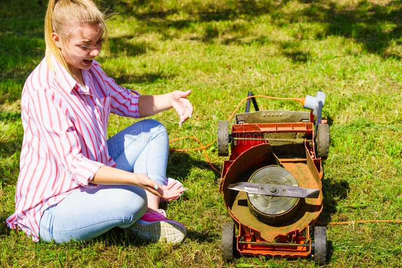 有残破的割草机的女性花匠 免版税库存照片