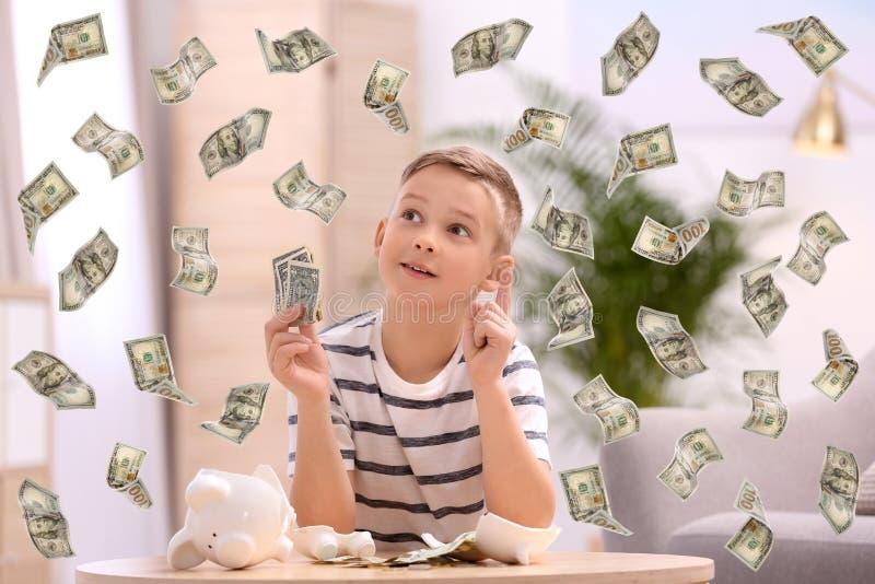 有残破的存钱罐和金钱的小男孩 库存照片