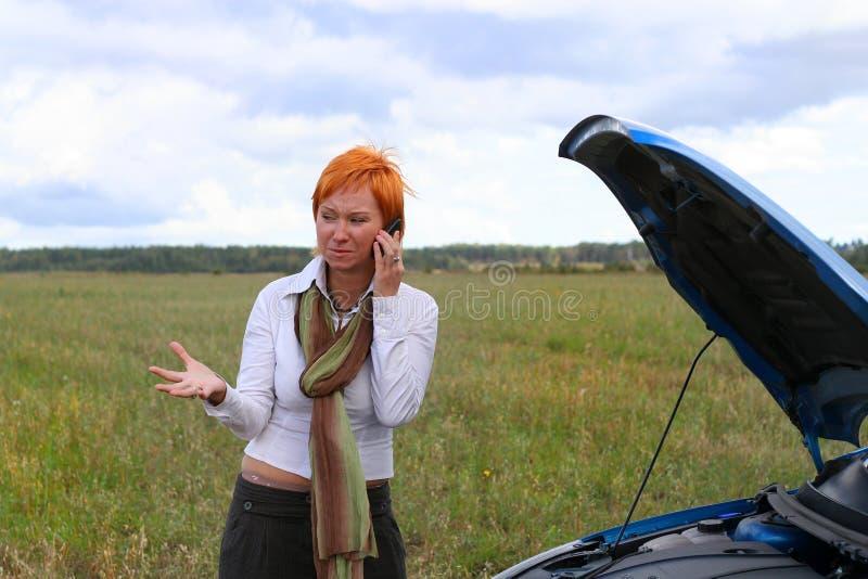 有残破的汽车的少妇。 免版税库存图片