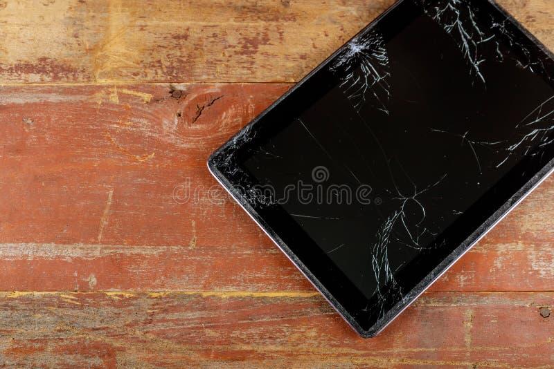 有残破的玻璃屏幕的片剂计算机在木背景 免版税库存照片