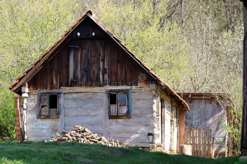 有残破的窗口和切好的堆的被放弃的老被毁坏的小木房子在前面的木柴位于在小山顶部 库存图片
