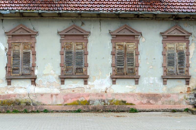 有残破的窗口和快门的被毁坏的房子 免版税库存图片