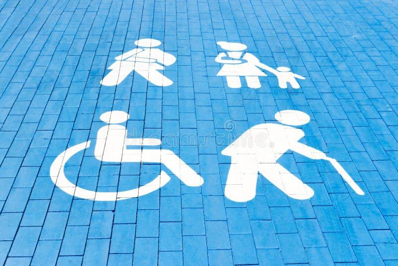 有残障的停车位、妈妈有孩子的,年长人和人有膏药的 在沥青的蓝色正方形 免版税库存照片