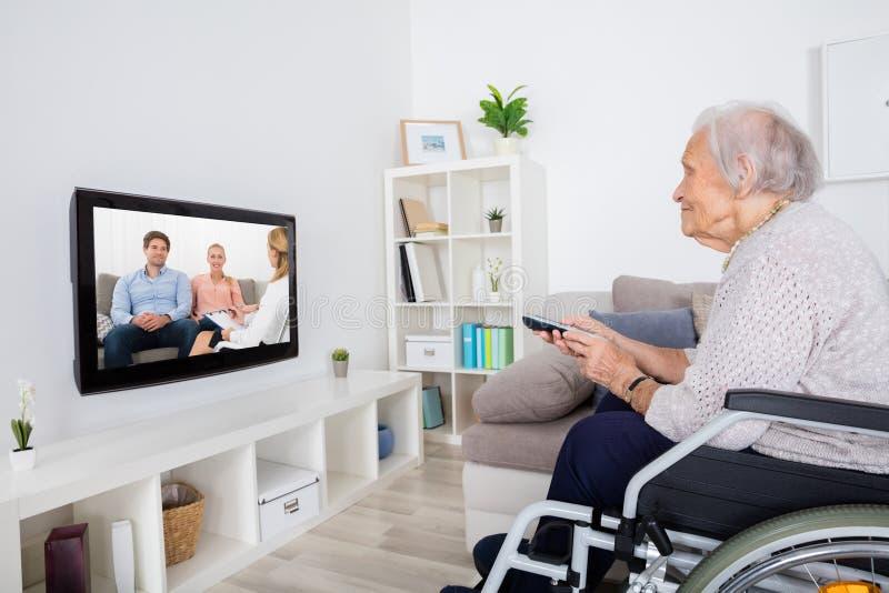 有残障的在电视上的祖母观看的电影 免版税库存照片