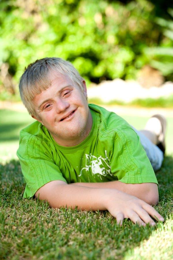有残障的男孩纵向绿草的。 免版税库存照片