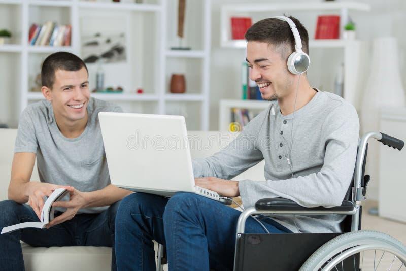 有残障的年轻检查在膝上型计算机的人和朋友音乐 免版税库存图片