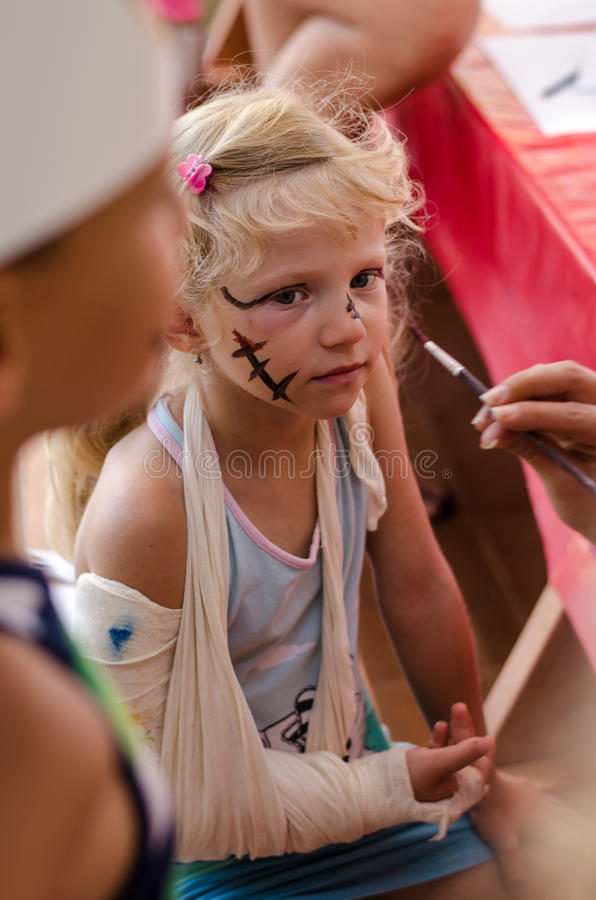 有残破的手和面孔绘画的小白肤金发的女孩 库存图片