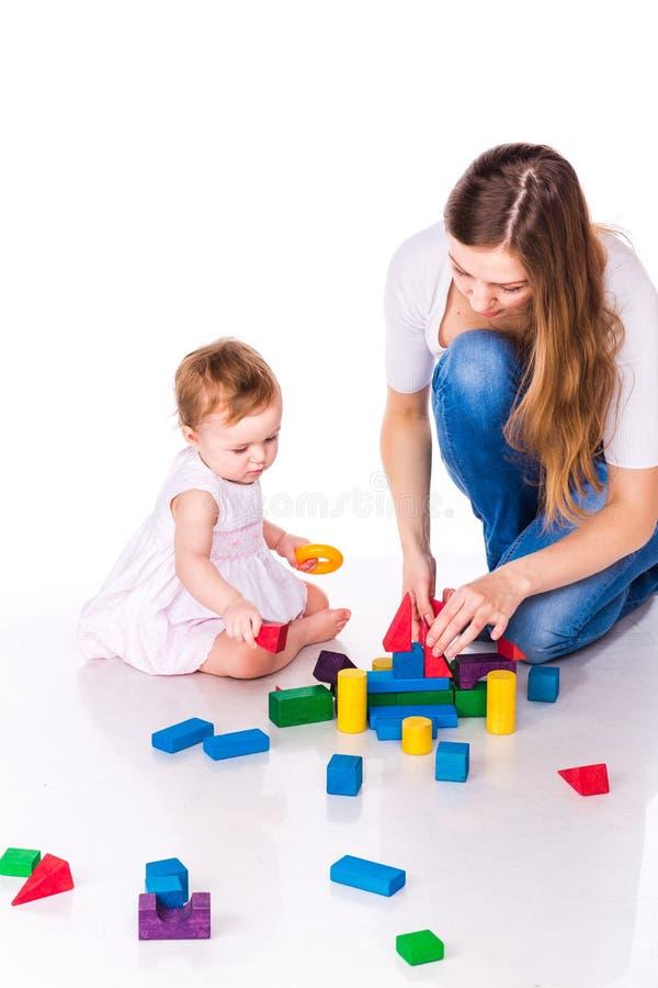 有母亲大厦的美丽的婴孩与立方体 库存照片