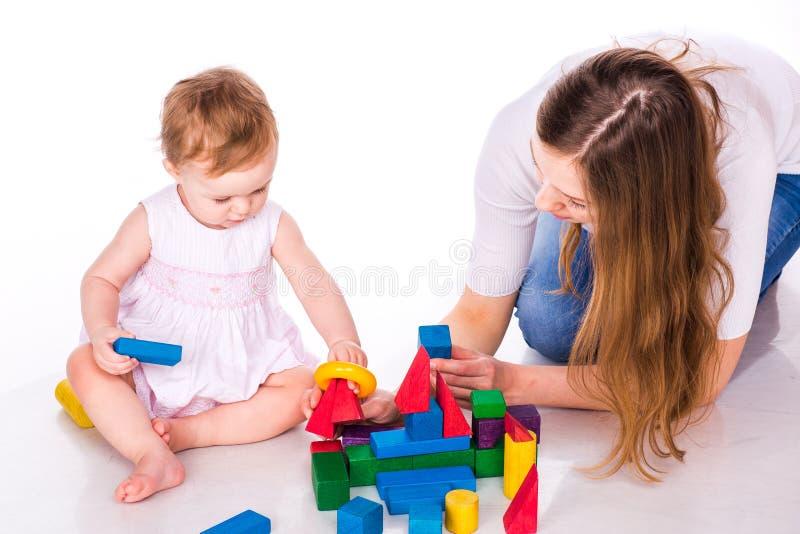 有母亲大厦的美丽的婴孩与立方体 免版税库存照片