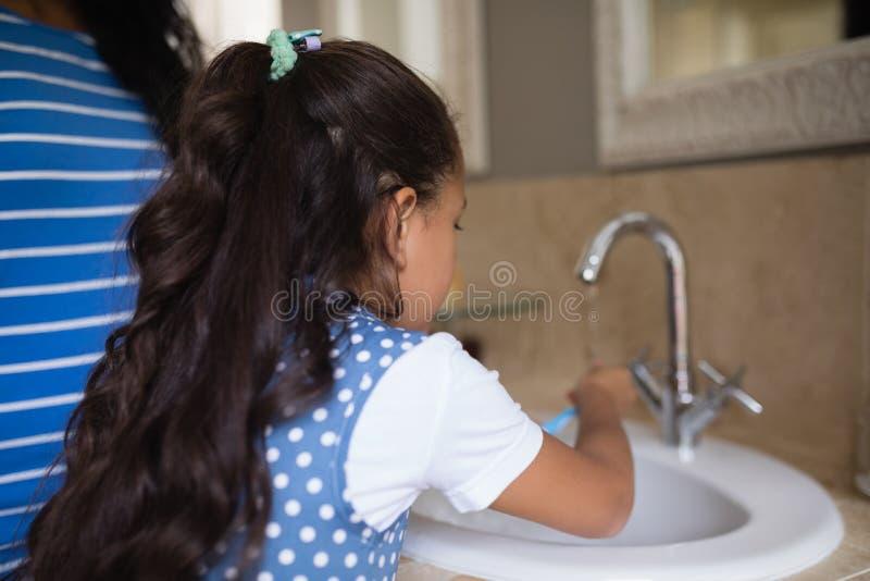有母亲掠过的牙的女孩在卫生间水槽 库存照片