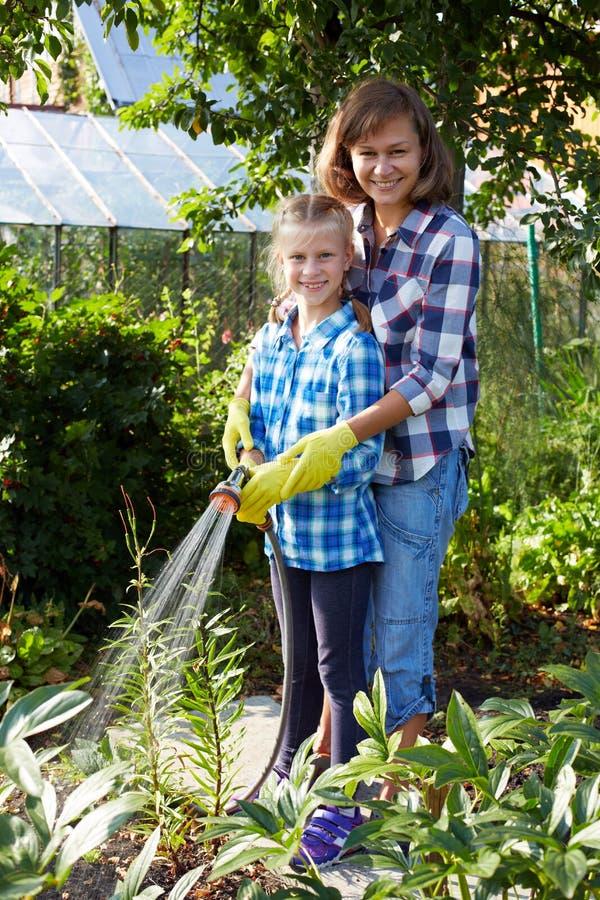 有母亲浇灌的花的小女孩在草坪 免版税库存图片