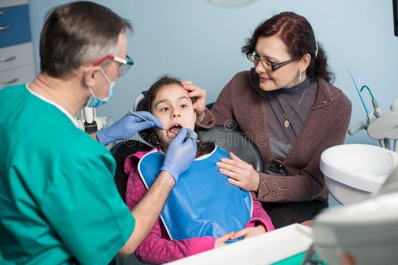 有母亲的女孩第一次牙齿参观的 做患者的小儿科牙医第一核对在牙齿办公室 库存图片